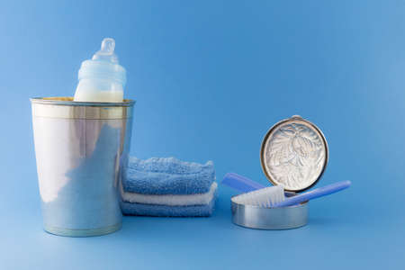 Baby boy luxurious items collection isolated on pale blue background. Milk bottle, comb, hairbrush, silver champagne bucket and can, towels.