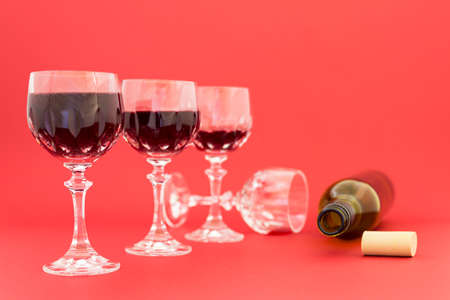 emptied: Concept of alcohol consumption, alcoholism and abuse with a line of beautiful crystal glasses filled with red wine and an empty bottle. Stages of drinking underlined by blurred image effect.