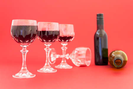 emptied: Concept of alcohol consumption, alcoholism and abuse with a line of beautiful crystal glasses filled with red wine, a full and an empty bottle. Stages of drinking underlined by blurred image effect. Stock Photo