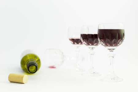 Concept of alcohol consumption, alcoholism and abuse with a line of beautiful crystal glasses filled with red wine and an empty bottle. Stages of drinking underlined by blurred image effect. Stock Photo - 79380730