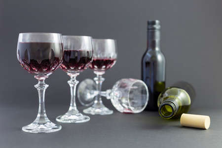 Concept of alcohol consumption, alcoholism and abuse with a line of beautiful crystal glasses filled with red wine, a full and an empty bottle. Stages of drinking underlined by blurred image effect. Stock Photo - 79380735