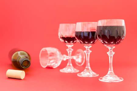 Concepto de consumo de alcohol, alcoholismo y abuso con una línea de hermosos vasos de cristal llenos de vino tinto y una botella vacía. Etapas de la bebida subrayadas por efecto de imagen borrosa.