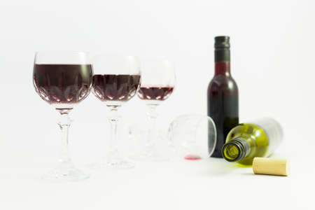 Concept of alcohol consumption, alcoholism and abuse with a line of beautiful crystal glasses filled with red wine, a full and an empty bottle. Stages of drinking underlined by blurred image effect. Stock Photo - 79576733