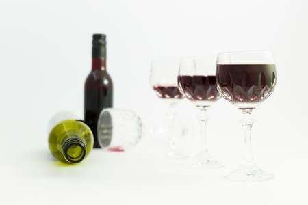 Concept of alcohol consumption, alcoholism and abuse with a line of beautiful crystal glasses filled with red wine, a full and an empty bottle. Stages of drinking underlined by blurred image effect. Stock Photo
