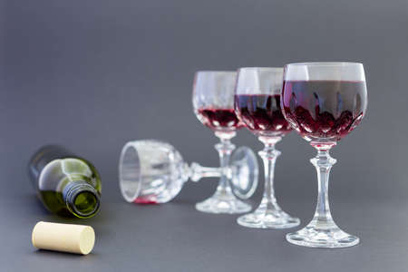 Concept of alcohol consumption, alcoholism and abuse with a line of beautiful crystal glasses filled with red wine and an empty bottle. Stages of drinking underlined by blurred image effect.
