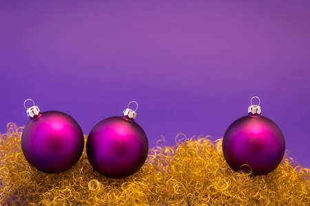 tinsel: Beautiful purple christmas balls with satin effect on gold glitter and purple background.