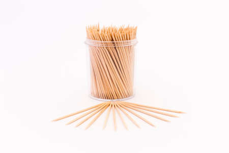 Wooden toothpicks in a transparent plastic container on white background