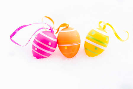 Closeup of pink, orange and yellow easter eggs with ribbons and decorated with stripes and dots laying outdoors on fresh snow in spring Stock Photo