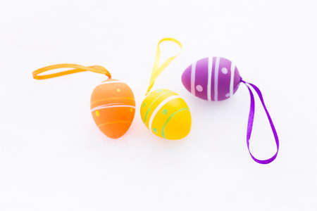 Closeup of purple, orange and yellow easter eggs with ribbons and decorated with stripes and dots laying outdoors on fresh snow in spring