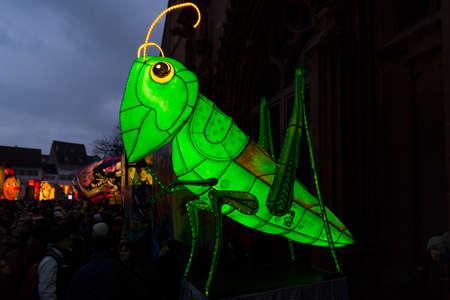 Muensterplatz, Basel, Switzerland - February 20th, 2018. Basel carnival. Beautiful illuminated carnival lantern in form of a green grasshopper
