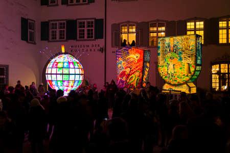 Muensterplatz, Basel, Switzerland - February 20th, 2018. Basel carnival. Three beautiful illuminated carnival lanterns with a watching crowd of people