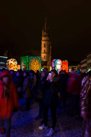 Muensterplatz, Basel, Switzerland - February 20th, 2018. Basel carnival. A young woman taking pictures with her smart phone. Basel minster with illuminated lanterns in the background