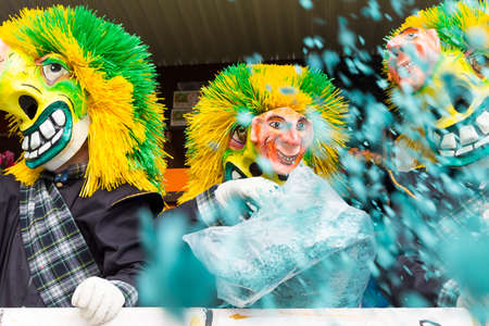 Basel carnival. Steinenberg, Basel, Switzerland - February 21st, 2018. Close-up waggis clowns throwing confetti into the crowd