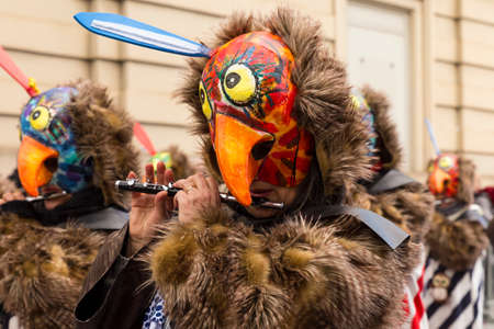 Basel carnival. Steinenberg, Basel, Switzerland - February 21st, 2018. Close-up of a carnival participant with a bird shaped mask Editorial