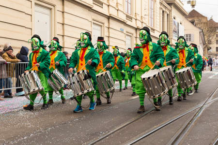 Basel carnival. Steinenberg, Basel, Switzerland - February 21st, 2018. Carnival group in green grasshopper costumes playing snare drums Editorial