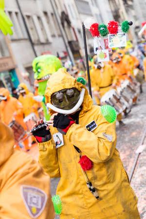 Basel carnival. Falknerstrasse, Basel, Switzerland - February 21st, 2018. Close-up of a carnival participant in orange costume