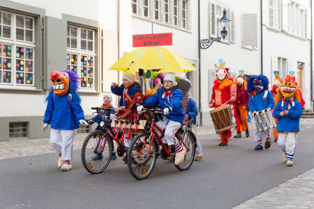 Basel carnival. Augustinergasse, Basel, Switzerland - February 21st, 2018. Group of children with a huge bike and colorful costumes Editorial