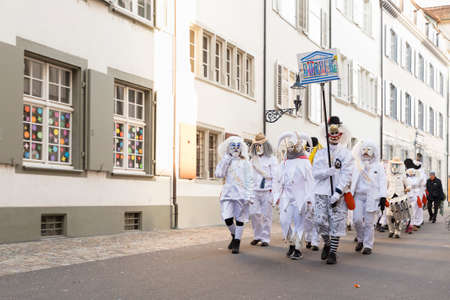 Basel carnival. Augustinergasse, Basel, Switzerland - February 21st, 2018. Carnival group in white costumes in the old town Editorial