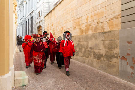 Basel carnival. Rheinsprung, Basel, Switzerland - February 21st, 2018. Group of revelers in red costumes in the old town