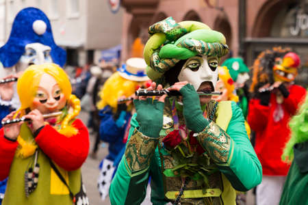 Basel carnival. Schnabelgasse, Basel, Switzerland - February 21st, 2018. Close-up of a flute playing reveler with a beautiful costume and mask Editorial