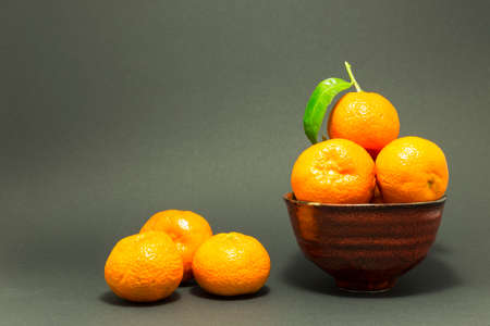 Still life studio shot of a red ceramic bowl with black texture filled with fresh orange tangerines on gray background. Stock Photo