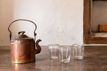 Still life with a beautiful worn retro style copper tea kettle with three empty glasses on a massive wooden table. Stock Photo