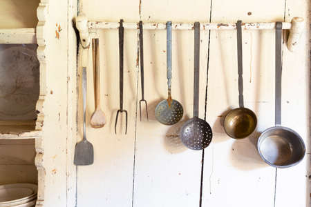 Retro style set of different wooden and metal kitchen spoons and tools hanging on a wall Stock Photo