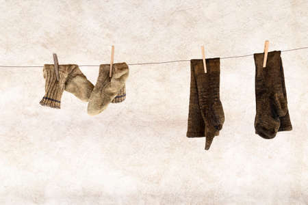 Two pairs of knitted woolen socks hanging on a laundry rope with wooden clothespins Stock Photo