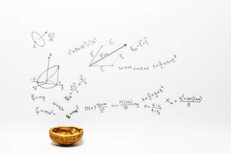 Concept of the phrase physics in a nutshell. Physics formulas drawn on white paper with a walnut shell