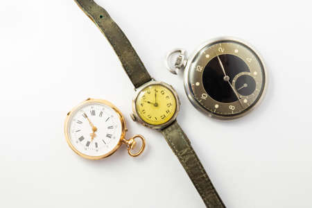 Set of watches on white background with a classic gold pocket watch a black and silver pocket watch and a wristwatch with worn leather straps Stock Photo