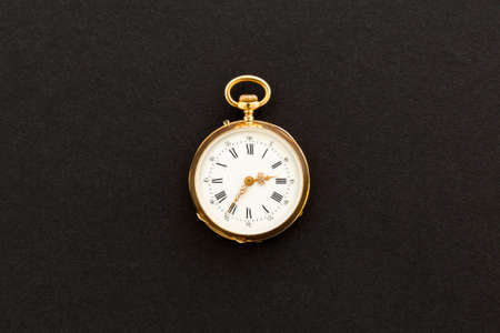 Closeup of a beautiful classic gold pocket watch on black background. Stock Photo