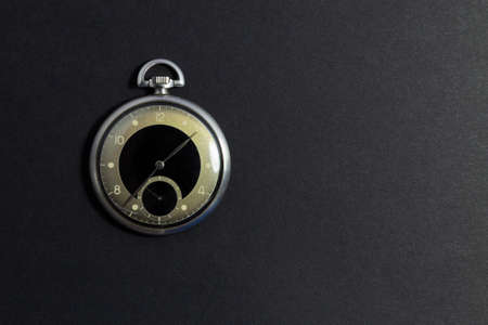 Closeup of a beautiful retro style black and silver pocket watch on black background.