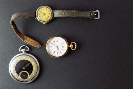 Set of watches on black background with a classic gold pocket watch a black and silver pocket watch and a wristwatch with worn leather straps Stock Photo