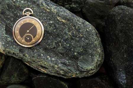 Closeup of a beautiful retro style black and silver pocket watch laying on wet green stones Stock Photo