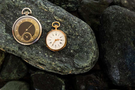 Set of watches, classic gold pocket watch and a black silver pocket watch on wet green stones