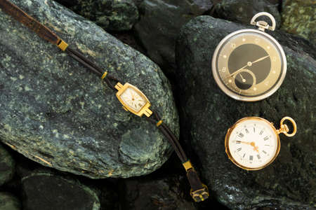 Set of watches, leathers wristwatch, classic gold pocket watch and a black silver pocket watch on wet green stone