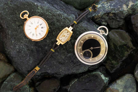 Set of watches on wet green stones with a classic gold pocket watch a black and silver pocket watch and a wristwatch with worn leather straps