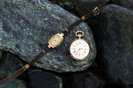 Set of watches on wet green stones with a classic gold pocket watch and a wristwatch with worn leather straps