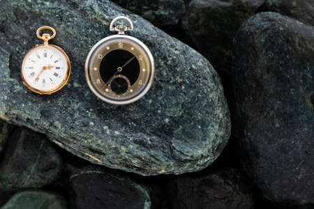 Set of watches on wet green stones with a classic gold pocket watch and a black and silver pocket watch