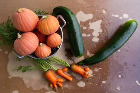Close-up of freshly harvested organic pumpkins, zucchinis and carrots on a table with flaking paint.