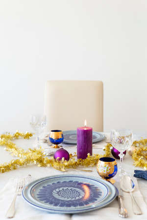 Close-up of a decorated dining table with burning candles, sterling cutlery, crystal glasses, colorful christmas balls and gold tinsel