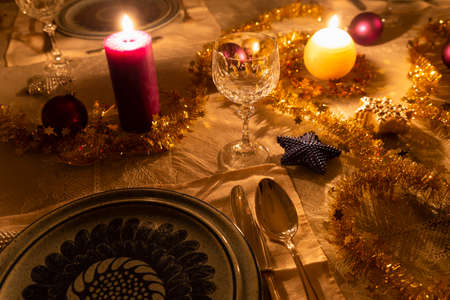 Detail view of a decorated dining table with burning candles, sterling cutlery, crystal glasses, colorful christmas balls and gold tinsel Stock Photo