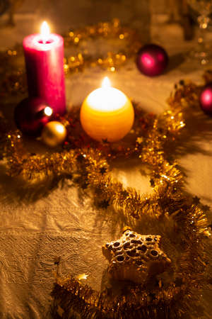 Christmas decoration details on a dining table. Burning candles, christmas balls, stars and gold tinsel