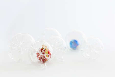 Still life with beautiful decorative transparent, red and blue christmas glass balls on white background