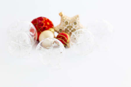 Still life with beautiful decorative transparent and red christmas glass balls and a satin colored star ornament on white background Stock Photo