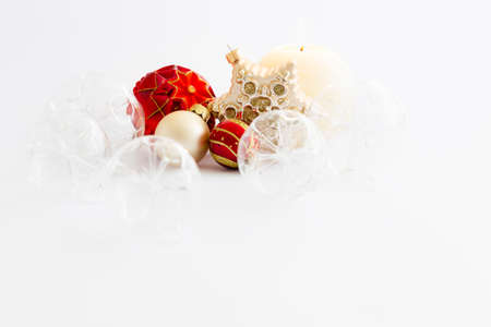 Still life with beautiful decorative transparent and red christmas glass balls, a round satin colored burning candle and a satin star ornament on white background Stock Photo