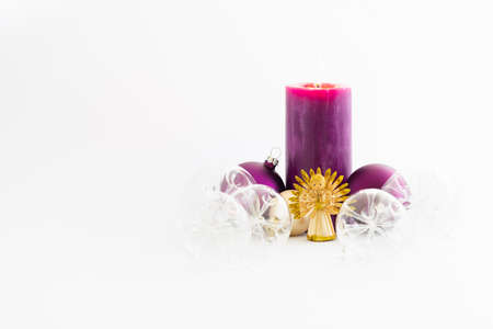 Still life with beautiful decorative transparent christmas glass balls, a purple colored burning candle and a straw angel on white background