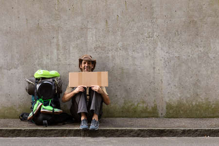 A single white adult man with a packed backpack sitting on the roadside in front of a gray wall hitchhiking with an empty cardboard sign