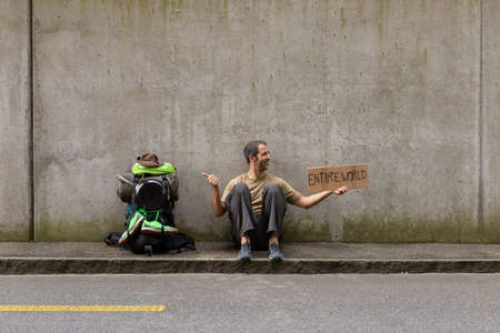 A single white adult man with a packed backpack sitting on the roadside in front of a gray wall hitchhiking with outstretched thumb and a cardboard sign reading entire world