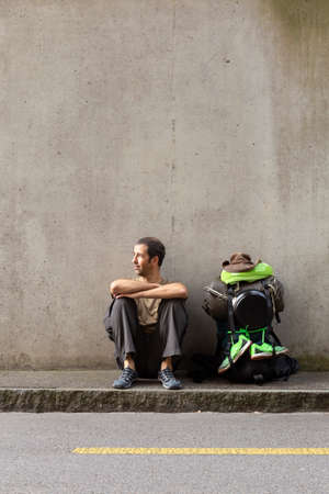 A single white adult man with a packed backpack sitting on the roadside in front of a gray wall taking a break from hitchhiking Stock Photo